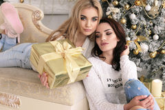 Beautiful girls in cozy home clothes celebrating New Year holida Stock Image