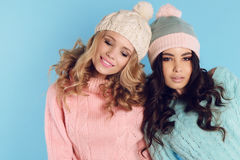 Beautiful girls with curly hair  in warm cozy winter clothes. Fashion studio photo of beautiful girls with curly hair  in warm cozy winter clothes Stock Image