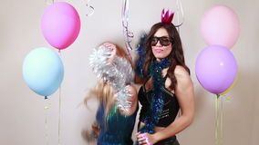 Beautiful girls dancing in photo booth. Two beautiful girls dancing in party photo booth stock video footage