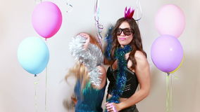Beautiful girls dancing in photo booth. Two beautiful girls dancing in party photo booth, graded stock footage