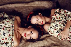 Beautiful girls with dark hair in dresses with prints of red poppies royalty free stock photography