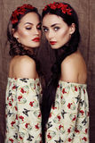 Beautiful girls with dark hair in dresses with prints of red poppies royalty free stock images