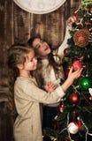 Beautiful girls decorating christmas tree Stock Images