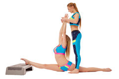 Beautiful girls doing stretching exercise in pair Royalty Free Stock Photos