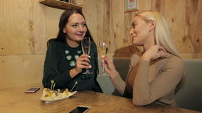 Beautiful girls drinking champagne in a cafe. Two girl friends sitting in a cafe drinking champagne and talking stock footage
