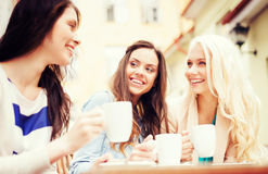 Beautiful girls drinking coffee in cafe. Holidays and tourism concept - beautiful girls drinking coffee in cafe Royalty Free Stock Photo