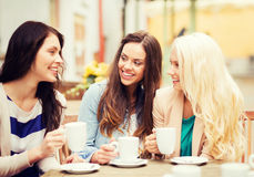 Beautiful girls drinking coffee in cafe. Holidays and tourism concept - beautiful girls drinking coffee in cafe Royalty Free Stock Photography