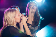 Beautiful girls drinking shots together. At the nightclub Royalty Free Stock Images