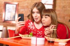 Beautiful girls eat sushi rolls at sushi bar. Stock Photo