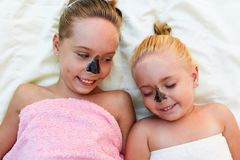 Beautiful girls with facial black clay mask. Stock Photography