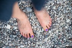 A beautiful girls feet at the beach, purple nail polish. Girl feet toes nail polish beach purple vacation pebble stone gravel sexy young holiday woman beauty royalty free stock photography