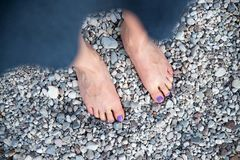 A beautiful girls feet at the beach, purple nail polish. Girl feet toes nail polish beach purple vacation pebble stone gravel sexy young holiday woman beauty royalty free stock image