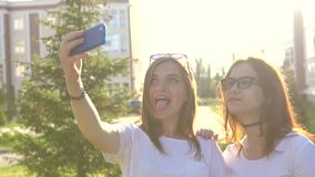 Beautiful girls friends taking selfies in the city sunset strong back light. Beautiful girls friends taking selfies in the city at sunset with strong back light stock video