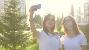 Beautiful girls friends taking selfies in the city sunset strong back light. Beautiful girls friends taking selfies in the city at sunset with strong back light stock footage