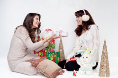 Beautiful girls giving christmas presents Royalty Free Stock Image