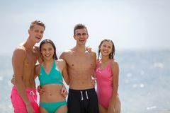 A company of laughing friends standing on a seashore in swimming suits on a natural blurred background. Royalty Free Stock Images