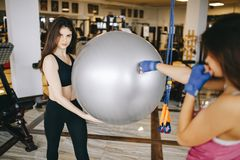 Two beautiful athletic girls are engaged in the gym stock image
