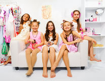 Beautiful girls with hair-curler sit on white sofa Royalty Free Stock Images