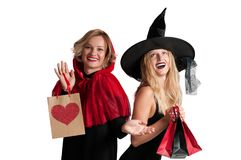 Beautiful girls in halloween costume witch and little red riding hood. On white background Stock Photos