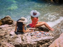 Beautiful girls in hats sunbathing Stock Images