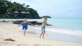 Beautiful girls have a lot of fun at tropical beach playing together. SLOW MOTION. Little girls having fun at tropical beach playing together at shallow water stock video