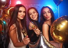 Party, holidays, celebration, nightlife and people concept - smiling friends dancing in club. Beautiful girls having party fun, drinking champagne. Holidays royalty free stock images