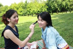 Beautiful girls helping their friend to makeup Stock Photography