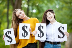 Beautiful girls are holding the dollar symbol. Two molodyu successful girl happily hold in their hands a dollar sign on the nature day in the park Royalty Free Stock Images