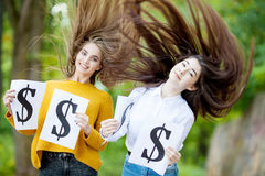 Beautiful girls are holding the dollar symbol. Two molodyu successful girl with long flowing hair  are holding dollar symbol on the nature of the day in the park Royalty Free Stock Photography