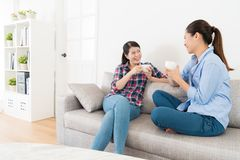Beautiful girls holding hot cup drinking coffee. Beautiful pretty girls holding hot cup drinking coffee sitting on sofa and looking each other sharing funny Royalty Free Stock Image