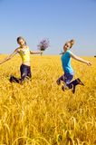 Beautiful girls jumps in golden field Stock Photography