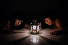 Beautiful girls are laying near the lantern Stock Images