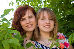 Beautiful girls look out from the bushes Stock Photo