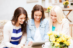 Beautiful girls looking at tablet pc in cafe Stock Image