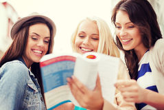 Beautiful girls looking into tourist book in city Royalty Free Stock Photo