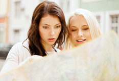 Beautiful girls looking into tourist map in city Royalty Free Stock Photography