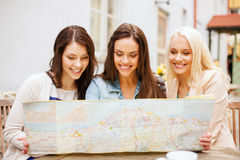 Beautiful girls looking into tourist map in city Royalty Free Stock Image