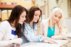 Beautiful girls looking into tourist map in city Royalty Free Stock Photo