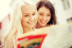 Beautiful girls looking into tourist map in city Royalty Free Stock Images