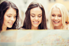 Beautiful girls looking into tourist map in city Stock Images