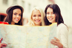 Beautiful girls looking into tourist map in city Royalty Free Stock Photos