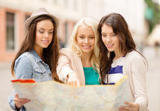 Beautiful girls looking into tourist map in city Stock Photos