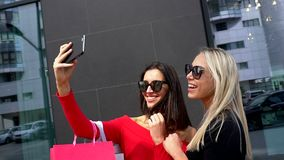 Beautiful girls make portert for memory on mobile phone camera. friends do selfie after shopping. Blonde and brunette in. Summer dresses on a background of stock video footage