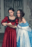 Beautiful girls in medieval dresses with scroll letter. Beautiful young girls in blue and red medieval dresses with scroll letter in the room Royalty Free Stock Photos