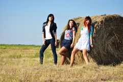 Beautiful girls near haystacks Stock Images
