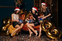 Beautiful girls opening Christmas gifts. Beautiful smiling girls in red Santa hat opening Christmas gifts at Christmas party Royalty Free Stock Photography