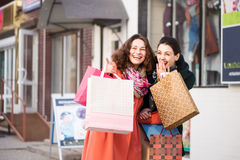 Beautiful girls with packages laughing while shopping Stock Images
