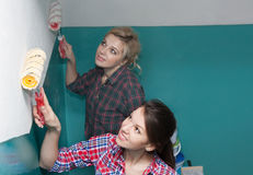 Beautiful girls and paint rollers Stock Photos