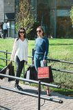 Beautiful girls with paper bags outside shopping mall. Young beautiful girls in sunglasses with paper bags standing outside shopping mall. Grass on a backgrond stock image