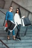 Beautiful girls with paper bags outside shopping mall. Young beautiful girls in sunglasses with paper bags walking on stairs out of shopping mall. Building on a royalty free stock photo